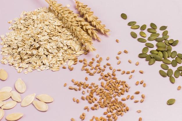 Spighette di frumento e fiocchi d'avena. semi di zucca e chicchi di grano sul tavolo. disposizione piatta. sfondo rosa