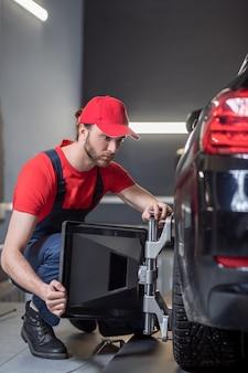 Allineamento delle ruote. giovane uomo adulto concentrato in tuta accovacciato vicino alla ruota anteriore con un dispositivo speciale in officina