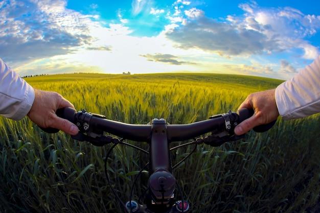 La ruota del primo piano ciclista contro un campo di grano alla luce del sole