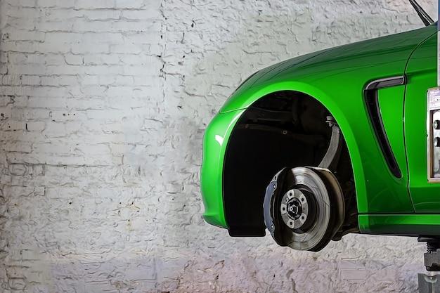 Servizio di sostituzione delle ruote automobile sportiva verde nella stazione di servizio per i freni delle sospensioni dei pneumatici sull'ascensore