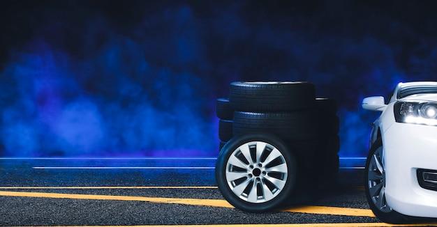 Mucchio di ruote e pneumatici sulla strada asfaltata e fumo blu con sfondo nero di notte