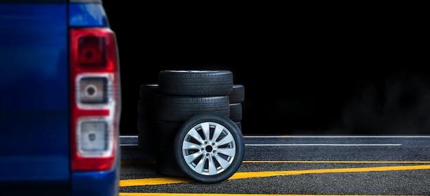 Mucchio di ruote e pneumatici sulla strada asfaltata con sfondo nero di notte