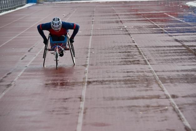 Atletica in sedia a rotelle. atleta maschio disabile in sedia da corsa che si prepara per una competizione importante mentre si allena da solo in pista all'aperto