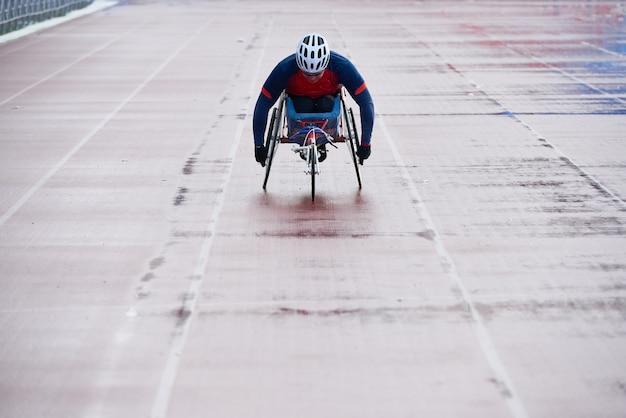 Atletica in sedia a rotelle. campione paralimpico in sedia a rotelle sportiva che si avvicina al traguardo mentre correva allo stadio di atletica leggera all'aperto