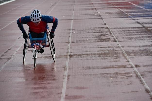 Atletica in sedia a rotelle. velocità di allenamento di atleta maschio con disabilità fisica volitiva sulla sedia da corsa allo stadio di atletica leggera all'aperto