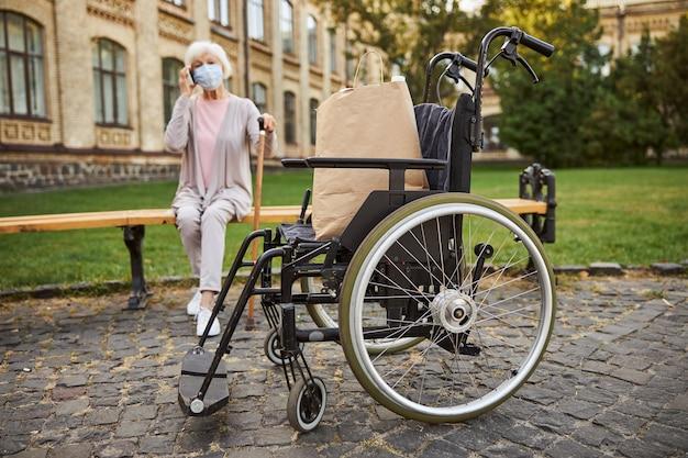 Sedia a rotelle nel parco. donna anziana sulla panchina che parla al telefono su uno sfondo