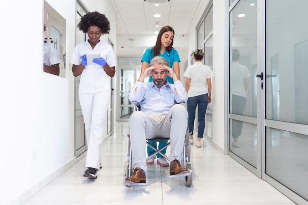 Paziente in sedia a rotelle con personale medico professionista femminile e infermiere specialista nel corridoio dell'ospedale