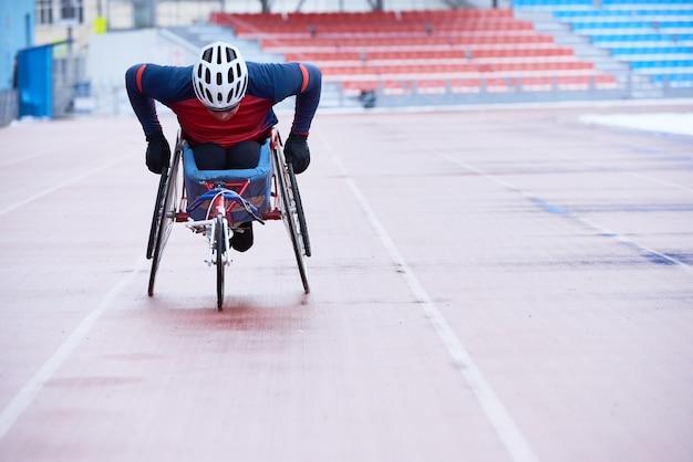 Corsa in carrozzina. sportivo portatore di handicap nel casco che copre la distanza in sedia a tre ruote specializzata su pista all'aperto