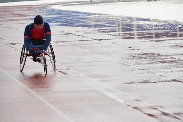 Corsa in carrozzina. atleta maschio handicappato volitivo in allenamento su sedia a rotelle sportiva allo stadio di atletica leggera all'aperto in una fredda giornata di pioggia