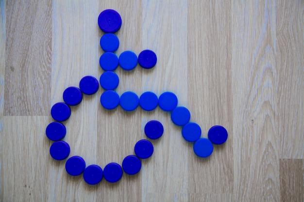 Segno di sedia a rotelle da tappi di plastica sfondo di tappi di bottiglia di plastica blu concetto di riciclaggio