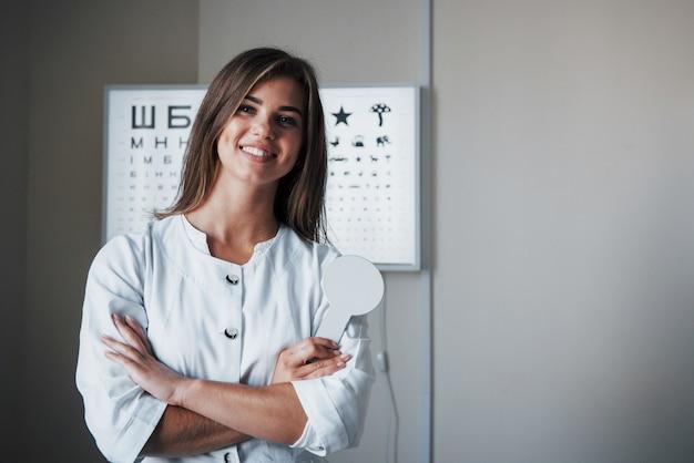 Quando sei innamorato del tuo lavoro. bella dottoressa in piedi in ufficio con le mani incrociate