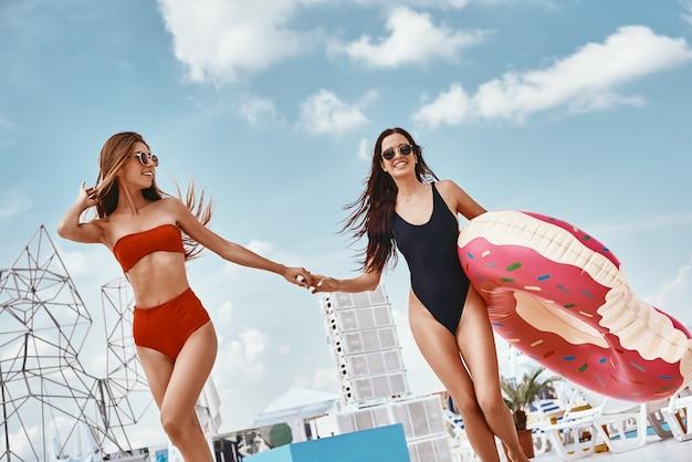 Dove splende sempre il sole ragazze che si divertono nella piscina sul tetto