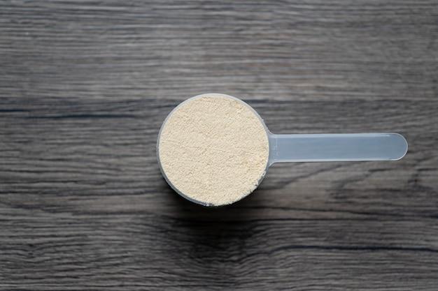 Proteine del siero di latte in polvere con misurino dosatore, integratore per bodybuilding sportivo.