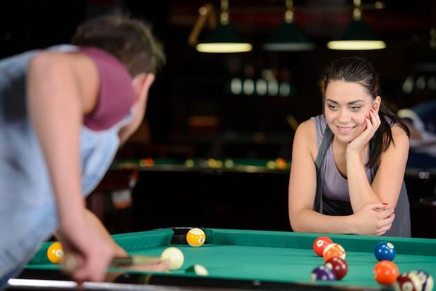 Mentre l'uomo colpisce la palla, la ragazza osserva attentamente.