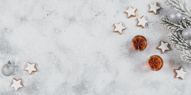 Whisky, brandy o liquore, biscotti e decorazioni natalizie su sfondo bianco. concetto di vacanze invernali. vista dall'alto, spazio libero per il testo