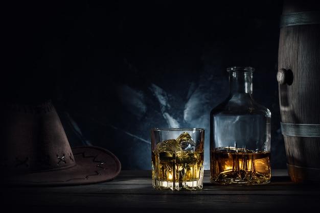 Whisky e cappello e botte su sfondo scuro
