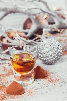 Whisky o liquore, caramelle al cioccolato al tartufo in polvere di cacao e decorazioni natalizie su fondo di legno bianco.