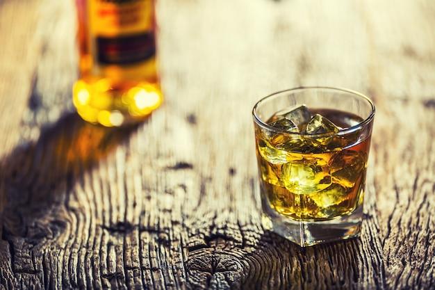 Whisky. bevanda di whisky con cubetti di ghiaccio sul vecchio tavolo in rovere rustico.