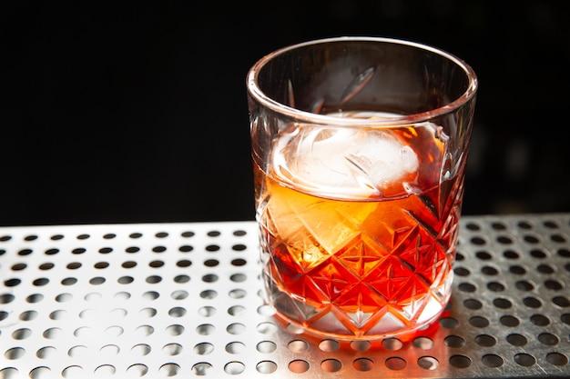 Whisky con una pallina di ghiaccio in un bicchiere pronto da mangiare