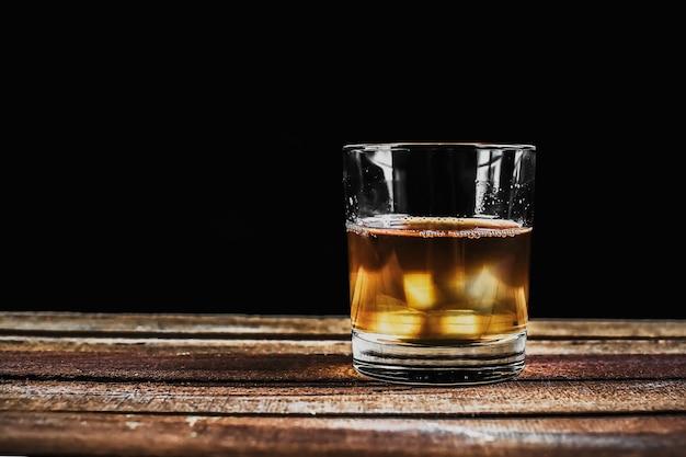 Whisky con cubetti di ghiaccio in bicchiere di roccia su tavola di legno