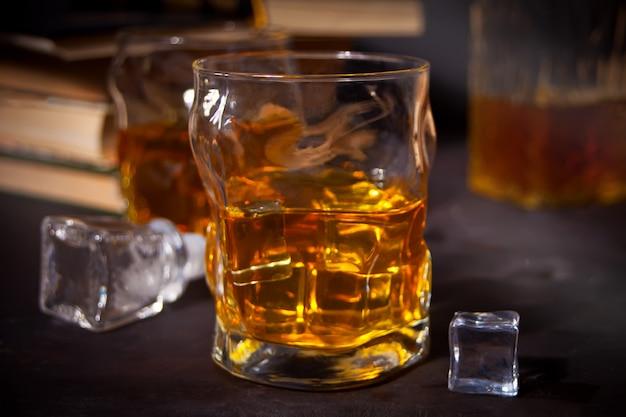 Whisky con ghiaccio su un tavolo di legno. libri antichi nelle vicinanze.