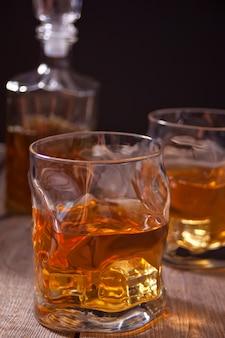 Whisky con ghiaccio su un tavolo di legno.