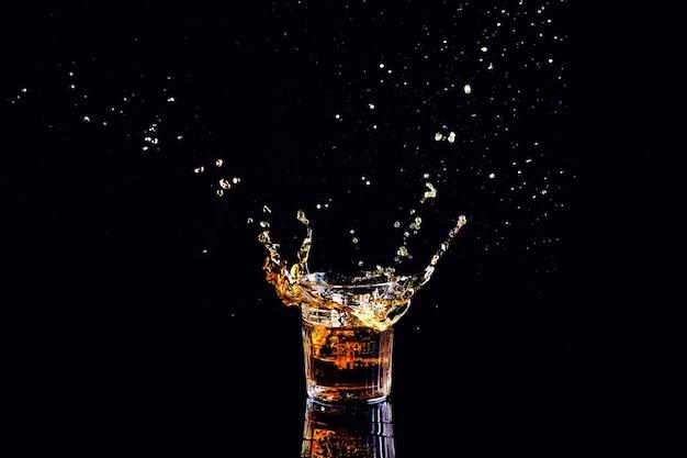Whisky con spruzzata sulla superficie nera, brandy in un bicchiere