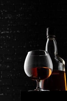 Bicchiere di whisky contro il muro nero scuro del grunge