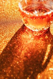 Whisky in un bicchiere su fondo dorato