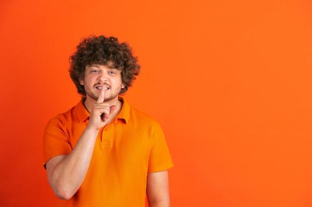 Sussurrare un segreto. ritratto monocromatico del giovane caucasico sulla parete arancione. bellissimo modello riccio maschio in stile casual.