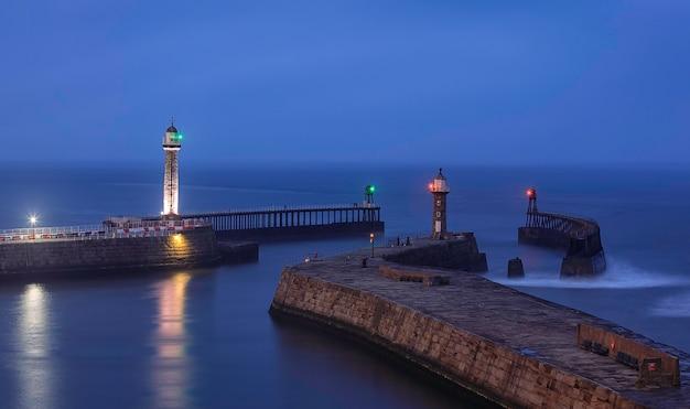 Porto di whitby. fari sui moli est e ovest. north yorkshire. mare del nord. inghilterra.