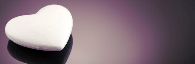 Cuore 3d bianco in polistirolo, su una superficie scura con posto per il testo