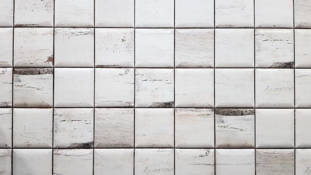 Fondo invecchiato bianco delle mattonelle. piastrelle texture senza soluzione di continuità. vecchie mattonelle sporche quadrate bianche piccole sul muro.