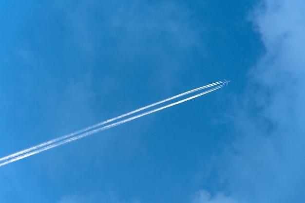 Grandi nuvole di scia di condensazione dell'aeroporto di aviazione dei due motori grandi dell'aereo bianco.