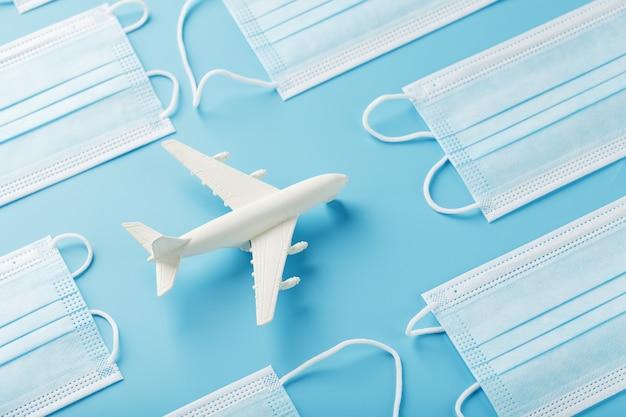 Aeroplano bianco intorno a maschere protettive su una superficie blu