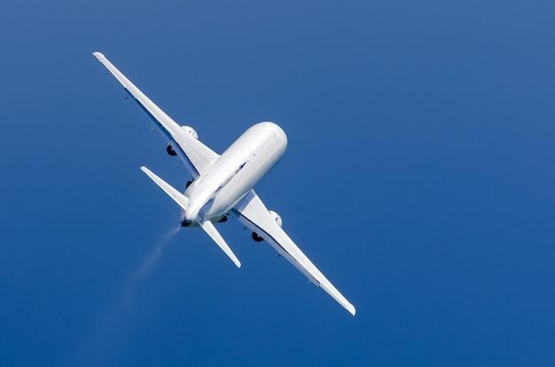 L'aeroplano bianco decolla sotto la pioggia nel cielo blu.