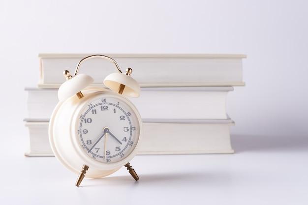 Sveglia bianca sullo sfondo della pila di libri sfondo chiaro