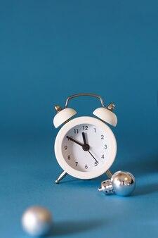 Sveglia bianca su un tavolo blu con palle di natale. il concetto delle decorazioni festive