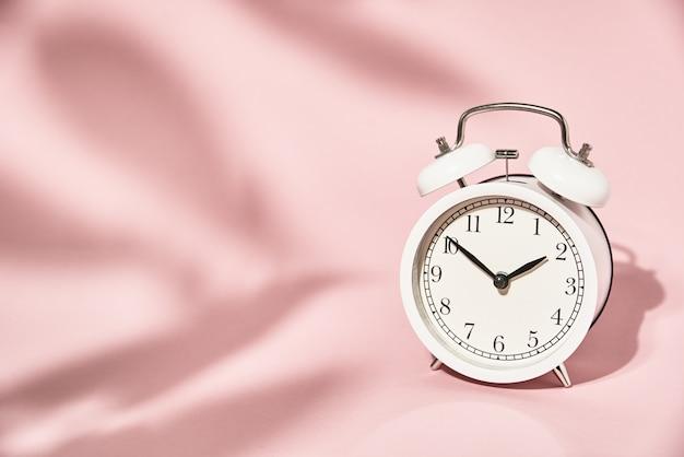 Sveglia bianca e lascia le ombre su sfondo rosa pastello. concetto di tempo minimo creativo