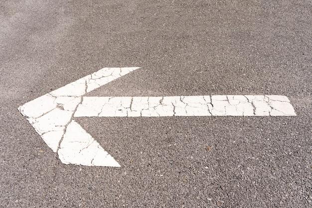 Freccia bianca sul pavimento in asfalto di un parcheggio per dirigere il traffico. Foto Premium
