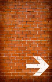 Freccia bianca dipinta su un muro di mattoni