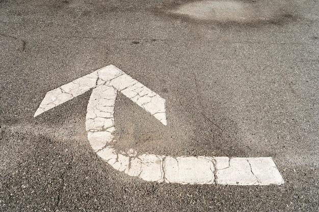 Freccia bianca che indica che è necessario svoltare incisa nell'asfalto di un parcheggio per dirigere il traffico.
