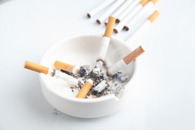 Posacenere bianco con una sigaretta. fumare