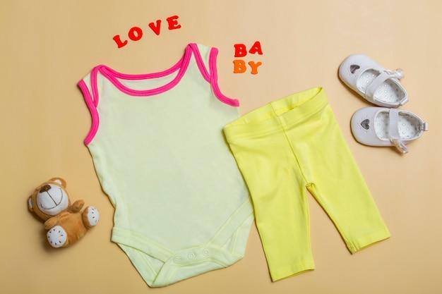 Body bianco per bambina su fondo beige con scarpe da bambino, un orsacchiotto, pantaloni gialli, un modello di body per neonati. disposizione piana, vista dall'alto.