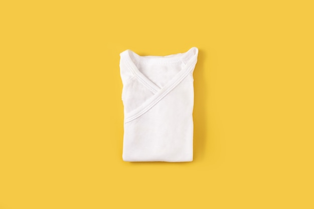 Tutina bianca per neonato su superficie gialla