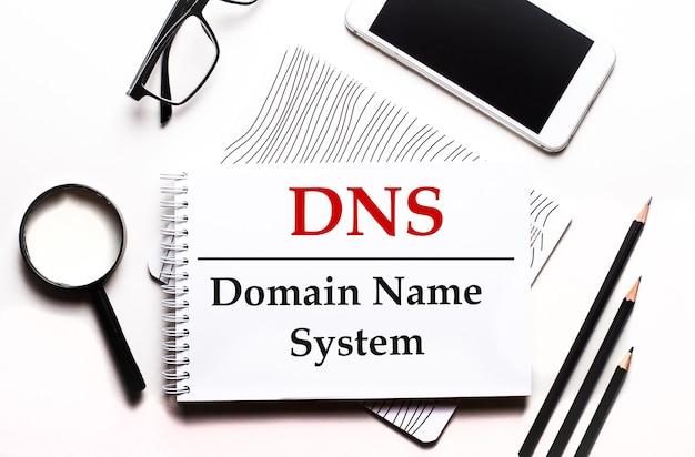 Su uno sfondo bianco occhiali, una lente d'ingrandimento, matite, uno smartphone e un notebook con il testo dns domain name system