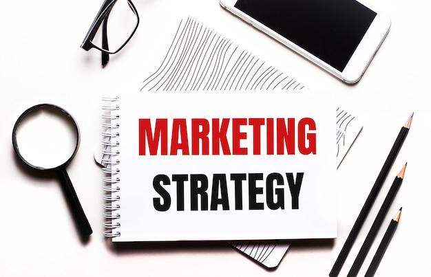 Su uno sfondo bianco occhiali, una lente d'ingrandimento, matite, uno smartphone e un taccuino con il testo strategia di marketing