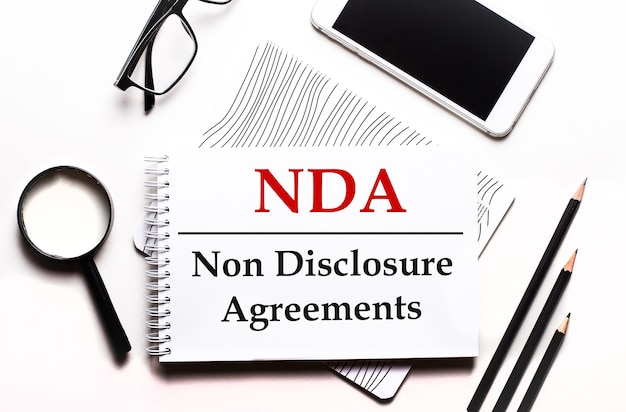 Su uno sfondo bianco occhiali, una lente d'ingrandimento, matite, uno smartphone e un taccuino con il testo nda non disclosure agreements