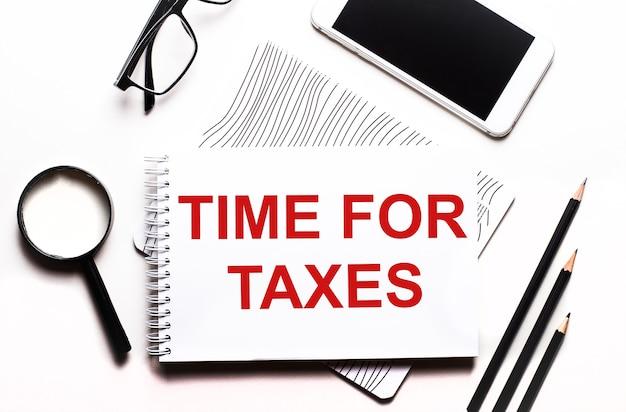 Su uno sfondo bianco occhiali, una lente d'ingrandimento, matite, uno smartphone e un taccuino con il testo time for taxes