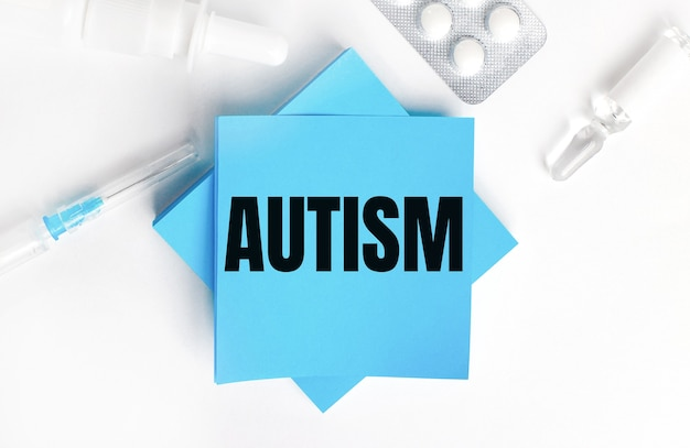 Su uno sfondo bianco, una siringa, una fiala, pillole, una fiala di medicinale e adesivi azzurri con la scritta autismo